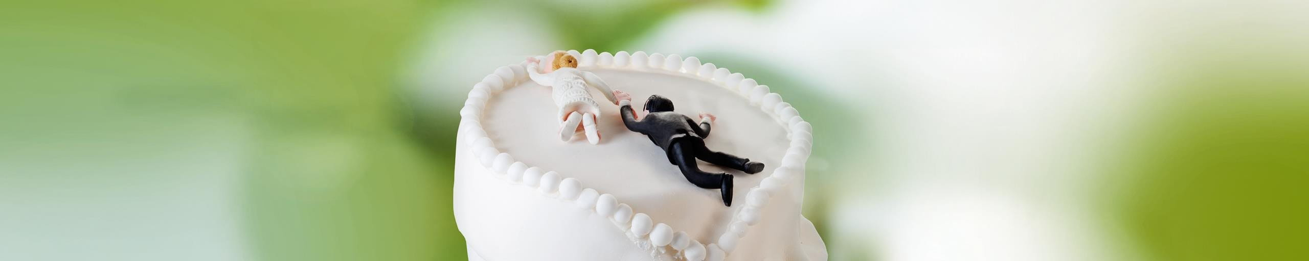 A wedding cake decorated with bride and groom figurines.