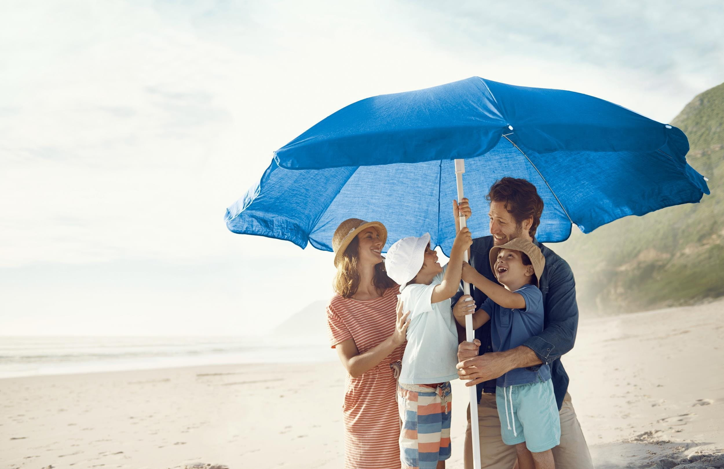 Family on beach with umbrella