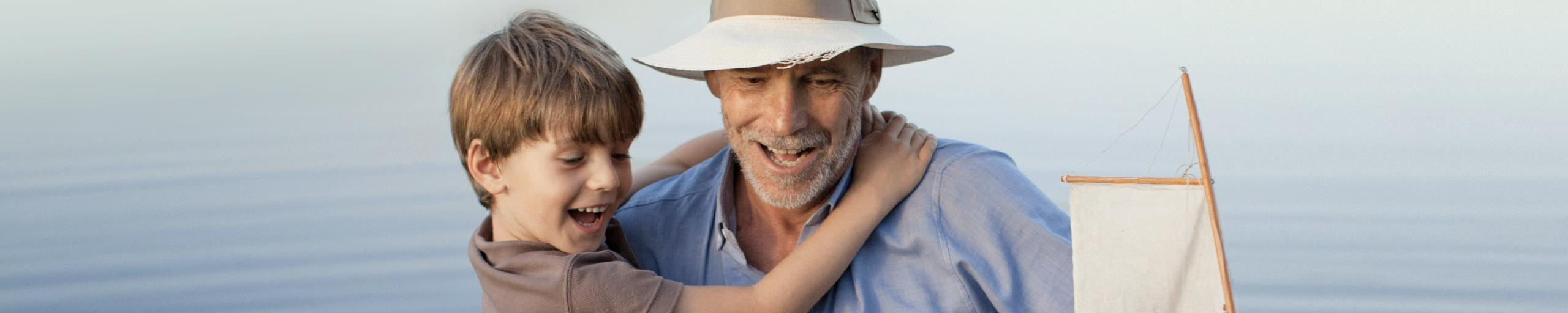 A boy in the arms of an elderly man.
